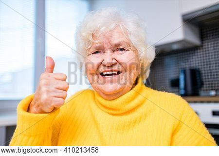 Senior Woman Showing Thumbs Up In In Living Room