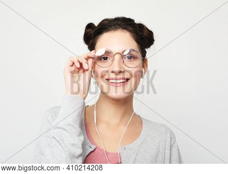 Young happy brunette woman girl wearing glasses isolated on light grey wall background studio portait. People lifestyle concept. Listen music with headphones.