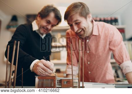 Young And Senior Adult Caucasian Architect Working At The Table With Project, Drawings Blueprint And