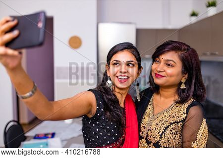 Two Indian Women In Saree Talk With Family By Phone Video Chatting At Living Room In Home