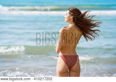 Topless Woman In Swimwear On The Beach With Her Hair Blowing In The Wind