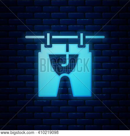 Glowing Neon Drying Clothes Icon Isolated On Brick Wall Background. Clean Shirt. Wash Clothes On A R