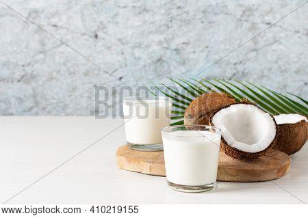 Two Glasses Of Coconut Vegan Milk With Coconut Halves On White Wooden Table. Alternative Vegan Nut M