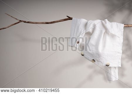 Clothes Concept. White Organic Linen Jacket Hanging On Dried Tree Branch. Shadow Shading On The Wall
