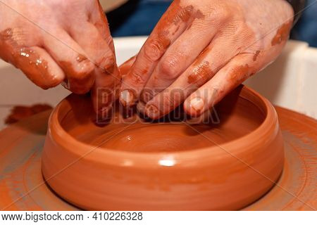 The Master Potter Uses His Fingertips To Shape The Edges Of The Earthenware Bowl On The Potter's Whe