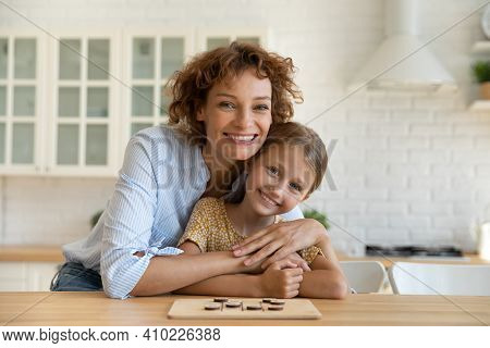 Affectionate Young Woman Parent Cuddle Girl Child By Kitchen Table