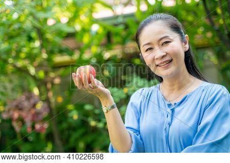 Beautiful Cheerful Asian Woman Eating Fresh Apple In Green Park
