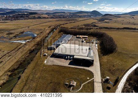 Miercurea Ciuc, Romania- 28 February 2021: Small Warehouse With Parking Cars Near Olt River.