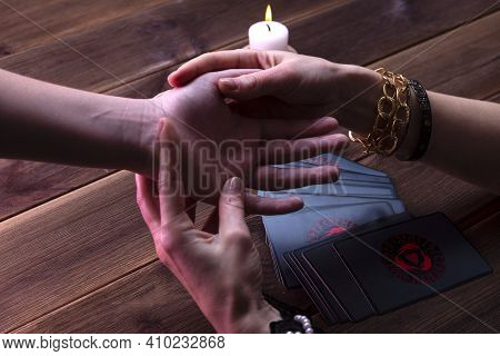 Minsk, Belarus, December 27, 2019. Fortune-teller's Hands With Predictions On A Wooden Background. F