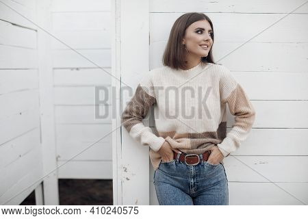 Young Woman In A Sweater On The Sandy Coast Of An Empty Beach In The Cool Weather In Early Spring. P
