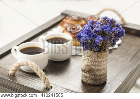 Two Cups Of Coffee On A Tray. A Bun And A Bouquet Of Flowers. Breakfast In Bed.