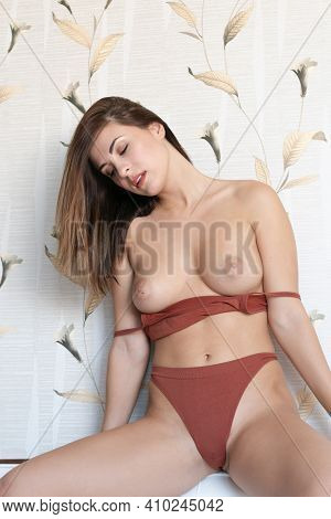 Young Beautiful Woman Posing In The Studio, Sitting On The Bed In Brown Lingerie