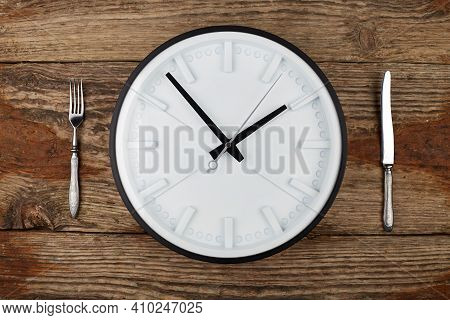 Concept. 10 Euros In A White Plate, Knife And Fork On A Wooden Background. Reverse.