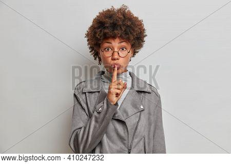 Studio Shot Of Secret Dark Skinned Curly Woman Makes Hush Gesture Presses Index Finger To Lips Tells