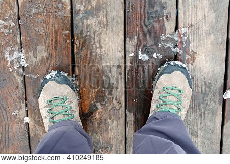 Tourist's Feet Shod In Pair Of Sport Trekking Boots On The Old Brown Wooden Boards Surface Outdoors