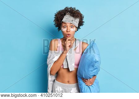 Surprised Curly Haired Woman Holds Chin And Looks Shocked Applies Collagen Patches Stares Bugged Eye