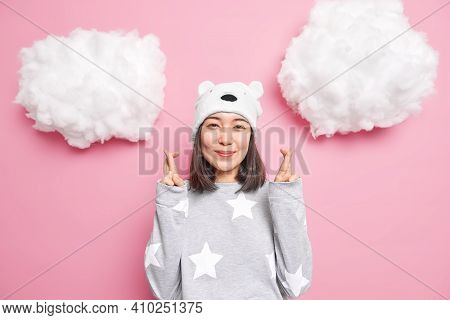 Hopeful Smiling Gentle Asia Woman Wears Pajama Bear Hat Crosses Fingers Waits For Good News Makes Wi