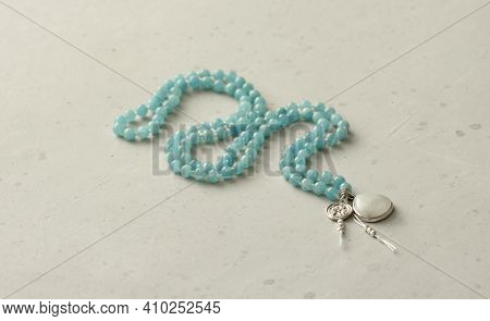 Rosary Mala 108 Beads From Natural Stones Aquamarine Lie On Light Modern Background. Author's Jewelr
