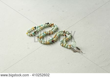 Rosary Mala 108 Beads From Natural Stones Amazonite Lie On Light Modern Background. Author's Jewelry