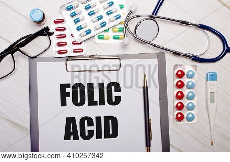 On A Light Wooden Background There Is Paper With The Inscription Folic Acid, A Stethoscope, Colorful