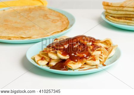 Blini Pancakes With Caramel, Dripping On A Spoon Levitation Close-up On A Blue Plate On A Light Back
