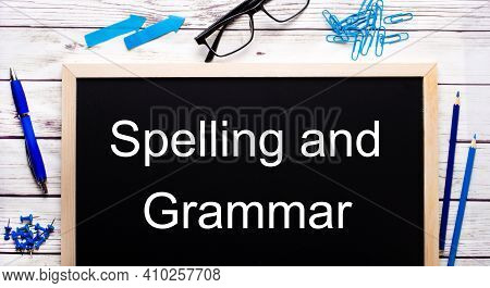 Spelling And Grammar Written On A Black Note-board Next To Blue Paper Clips, Pencils And A Pen.