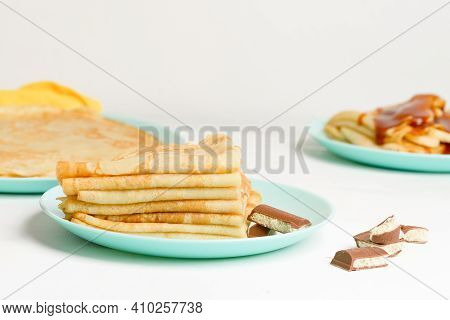 Blini Pancakes With Banana And Caramel, Close-up On A Blue Plate On A Light Background . Traditional