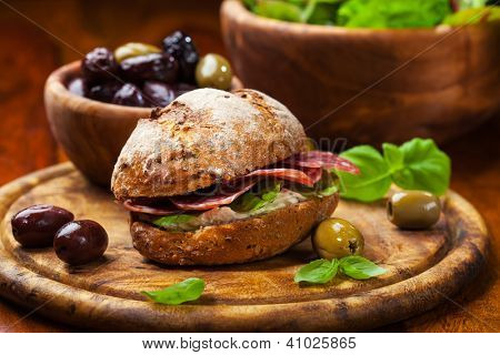 Sandwich with Italian salami, goat cheese and fresh olives