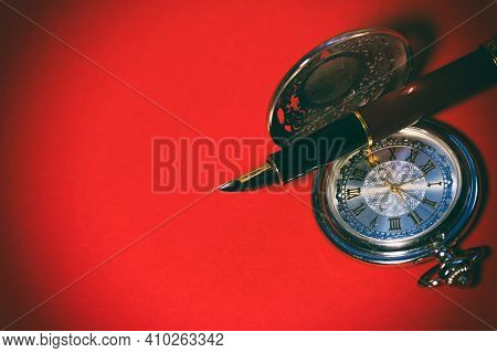 Beautiful Pocket Watch And Fountain Pen Close Up On A Red Background