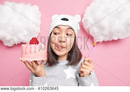 Pretty Asian Woman Looks With Temptation At Delicious Strawberry Cake Licks Lips Holds Toothbrush Wa