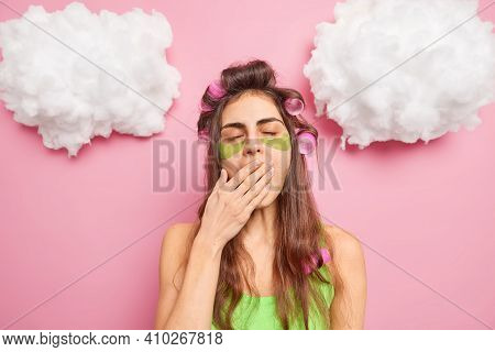 Tired Sleepy Woman Yawns And Covers Mouth Being Exhausted Of Beauty Therapies Applies Hair Rollers A