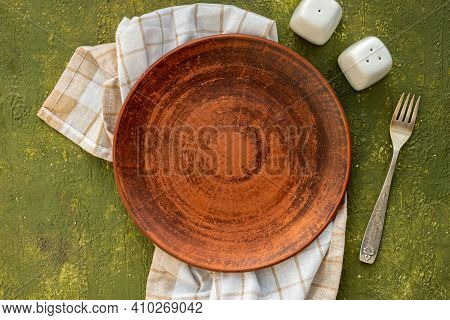 Table Setting On Olive Concrete Background: Empty Brown Earthenware Plate, Containers For Salt And P