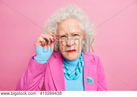 Portrait Of Scrupulous Granny Has Attentive Gaze At Camera Bad Eyesight Keeps Hand On Rim Of Spectac