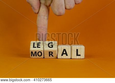 Moral Or Legal Symbol. Businessman Hand Turns Wooden Cubes And Changes The Word 'moral' To 'legal' O