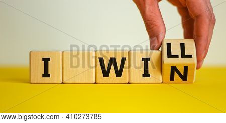 I Will Win Symbol. Businessman Turns Cubes And Changes Words I Will To I Win. Beautiful Yellow Table
