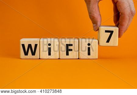 Wifi 7 Symbol. Businessman Holds A Wooden Cube With Words Wifi 7. Beautiful Orange Background, Copy