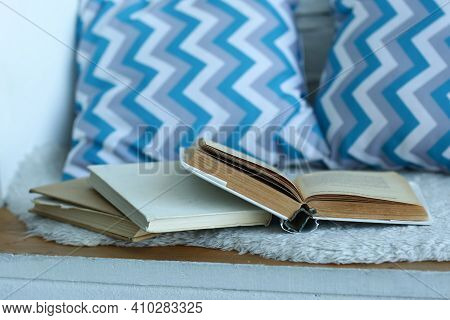 Opened Book With Blue Pattern Pillows In The Bedroom Close Up Photo