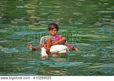 Semporna. Malaysia. November 28, 2018. Children Of Sea Gypsies Swim In The Sea On Polypropylene Bags