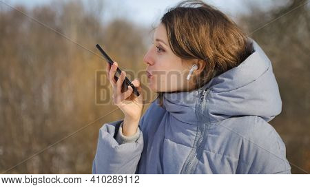 Young Woman With Wireless Headphone Is Using Her Smartphone To Send A Voice Message To A New Social