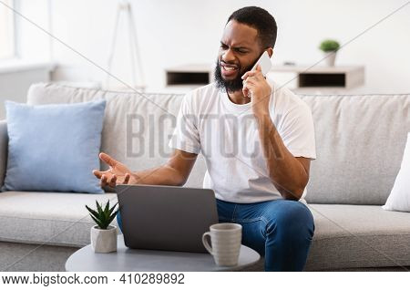 Unpleasant Call. Irritated Black Man Talking On Phone Having Problem With Laptop Or Internet Connect