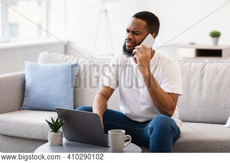 Displeased African Man Talking On Mobile Phone Sitting At Laptop Having Problem With Customer Suppor
