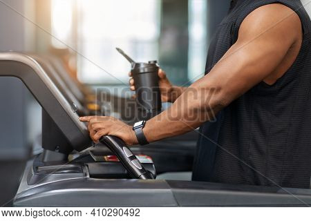 Cropped Of Muscular African American Man Holding Sports Drink, Standing On Treadmill, Drinking Prote