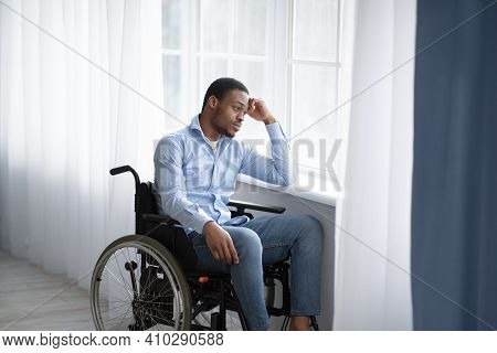 Unhappy Black Handicapped Guy Looking Out Window, Feeling Sad And Desperate At Home, Copy Space. Afr