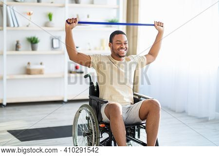 Happy Black Disabled Man In Wheelchair Doing Exercises With Rubber Band At Home. African American Ha