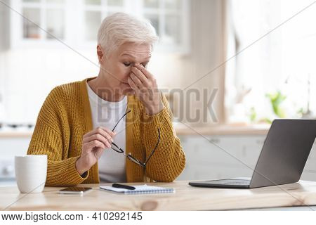 Tired Mature Grey-haired Woman Freelancer Working From Home, Using Laptop, Sitting In Kitchen, Copy