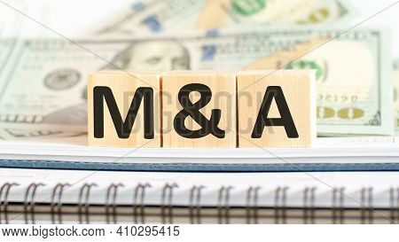 M And A. M A Short For Mergers And Acquisitions. Business Concept On Wooden Cubes And Dollars Backgr