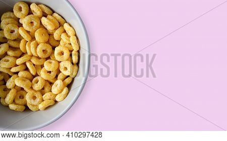 Bowl Of Breakfast Cereal In Pink Background. Healthy Cereal Rings. Space For Text. Top View. Flat La