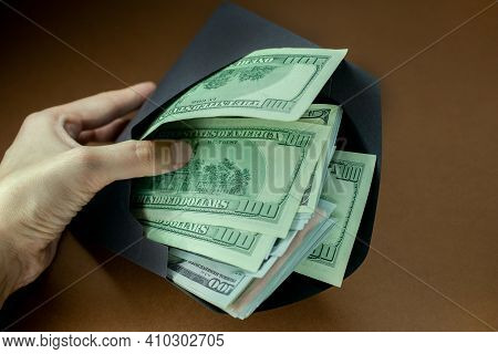 Money In An Envelope. Dollars In A Black Envelope. Concept: Illegal Salary. Tax Evader