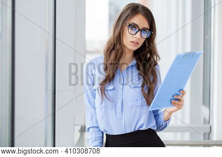 Young Business Woman With Clipboard In The Office.
