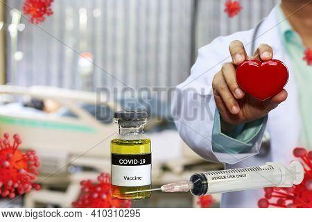 Coronavirus Covid-19 Vaccine In Bottle And Syringe For Against Virus With Doctor Holding Red Heart I